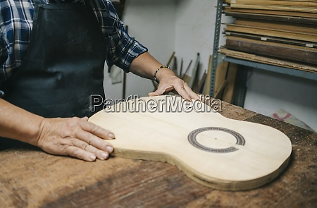 craftsman making guitar while standing by