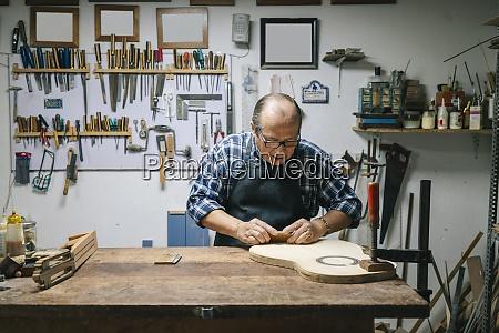 craftsman manufacturing guitar at workshop