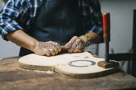 luthier carving guitar wood while standing