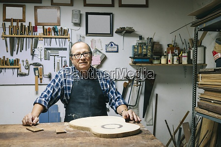 smiling man standing by workbench at
