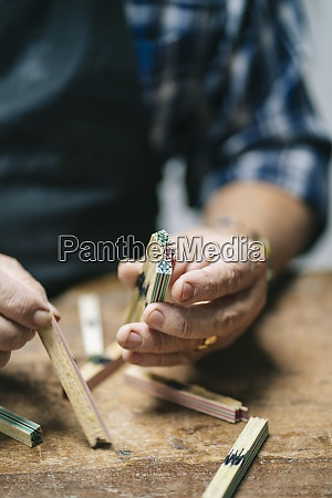 luthier holding wood stick while working