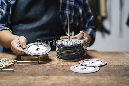 luthier selecting paper disk while standing
