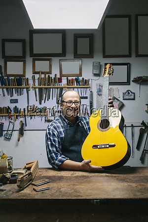 smiling craftsman holding guitar while standing