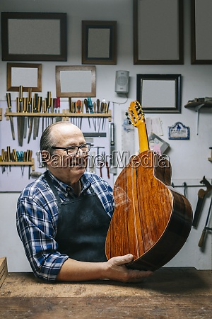man smiling while holding guitar by