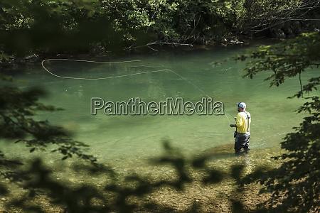 man fly fishing in savinja river