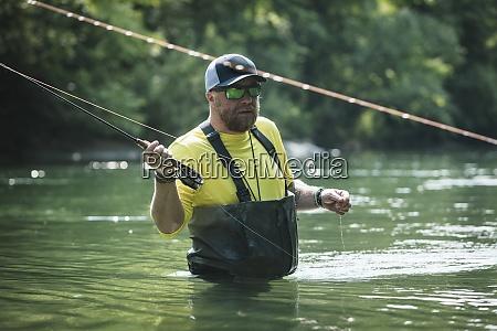 portrait of man fly fishing in