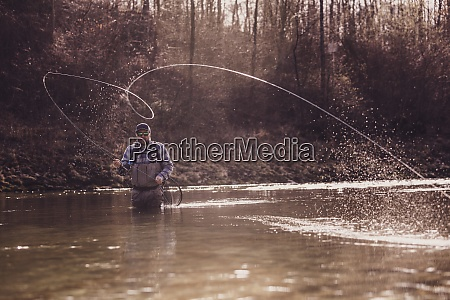 mid adult man throwing fishing reel