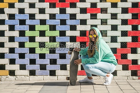 young woman crouching while holding skateboard