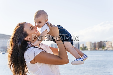 smiling mother picking up baby son
