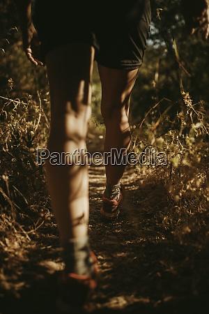 female trekker walking on narrow path