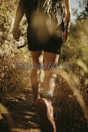 trekker with backpack walking on narrow