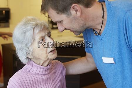 geriatric nurse talking to age demented