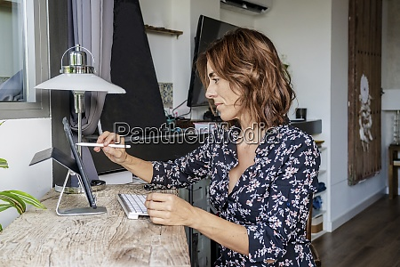 woman using digital tablet while sitting