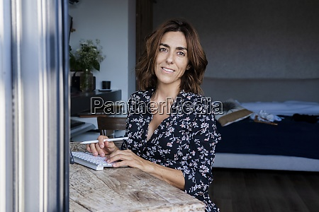 smiling woman siting by table at