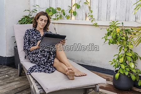 mature woman using digital tablet while