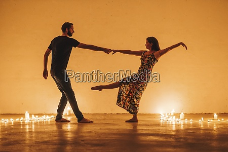 couple holding hands while dancing by