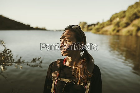 woman trekking by river across sierra