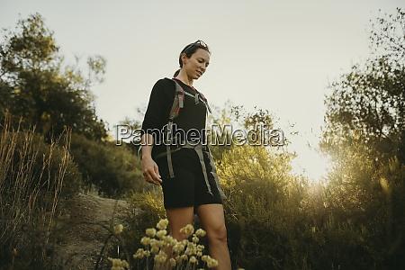 mid adult woman trekking on footpath