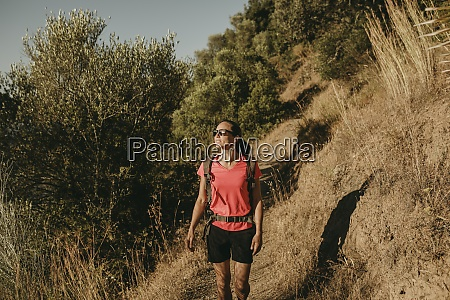 smiling woman trekking on mountain at