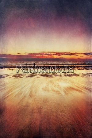 three walkers on the beach at
