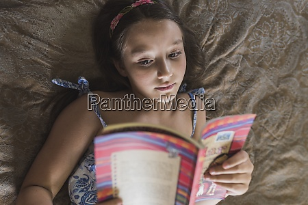 girl reading book while lying on