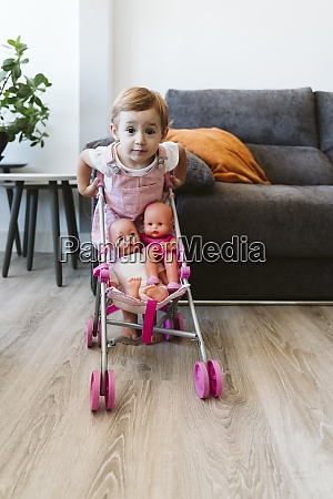 baby girl playing with baby stroller