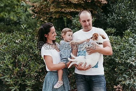 family standing with pet dog in