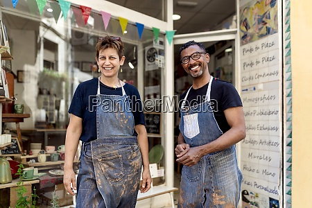 smiling coworkers wearing aprons standing outside