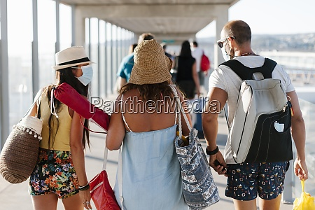 friends wearing masks walking on gangway