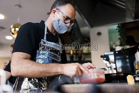 male barista wearing face mask while