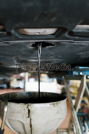 dirty oil draining from car in