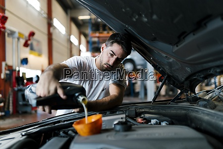 auto mechanic filling engine oil while