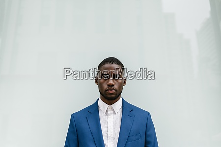 confident young businessman standing against window
