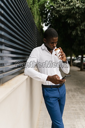 businessman drinking from cup while using
