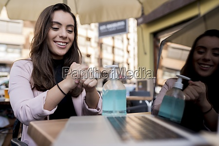 smiling young businesswoman using hand sanitizer