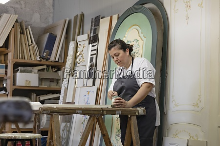mature woman painting door while standing