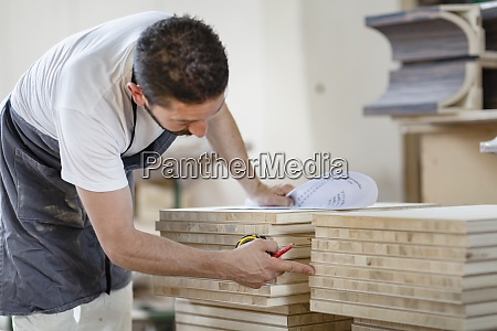 man counting wood plank while working