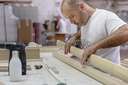 carpenter applying glue on wood while