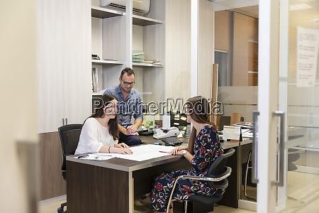designer team discussing plan sitting in