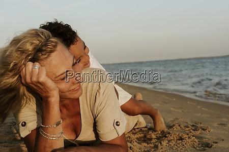 grandmother lying on sand while grandson