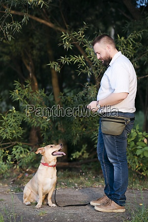 mid adult man standing with pet