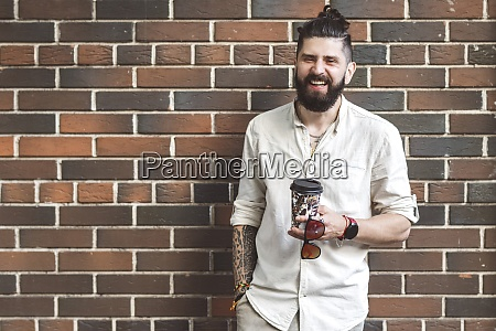 happy hipster man holding disposable cup