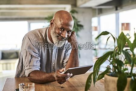 smiling mature man holding digital tablet