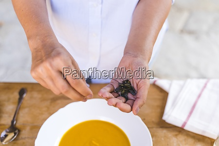 woman hand holding black coffee bean