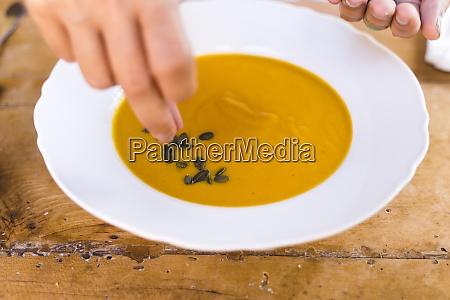 woman hand garnishing soup with black