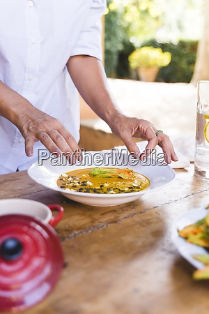 woman garnishing food for lunch on