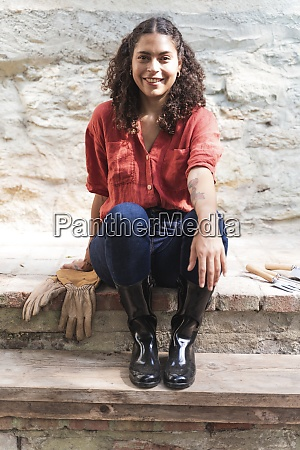 smiling mature woman sitting against wall