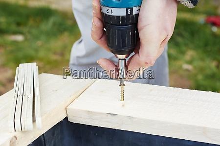 gardener screwing on wooden plank to