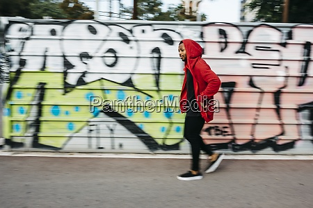 young man wearing red hoodie passing