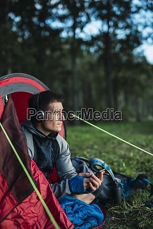 man camping in estonia sitting in
